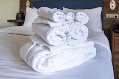 Clean towels on white bed. stock images