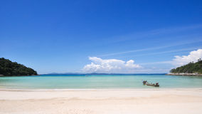 Clean tropical white sand beach and blue sky. Clean and pure view of tropical white sand beach and ocean and sky, with single boat floats ashore. Shot  on Raya Royalty Free Stock Image