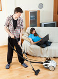 Clean up man, while wife lying with notebook Royalty Free Stock Photo