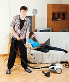Clean up man, while wife lying with notebook Royalty Free Stock Photography