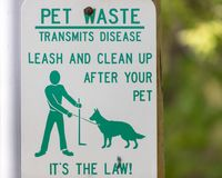 Clean Up Pet Waste Sign. Park sign asking you to pick up your pets waste Stock Images