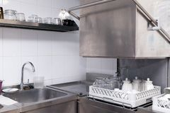 Clean utensils in the dishwasher. Wine glasses, beer mugs, ceramic teapots. Concept of preparation for opening, banquet, catering stock photography
