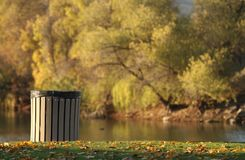 An environmentally friendly trash can at the park. A clean waste can at the lake in the fall with leaves falling Royalty Free Stock Photo