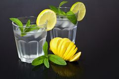 Clean water in a glass of ice cubes, lemon and fresh mint. Royalty Free Stock Photography