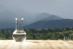 Clean water in a glass laboratory flask on wooden table on mountain background. Ecological concept, the test of purity. Clean water in a glass laboratory flask royalty free stock images