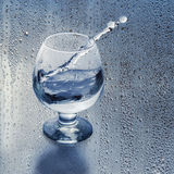 Clean water in the glass and splash on the background of the drops. Royalty Free Stock Image