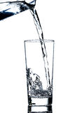 Clean water poured from a jug into a glass. Over white background Stock Images
