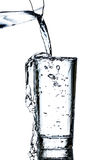 Clean water poured from a jug into a glass. Over white background Stock Photography