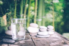 Clean water pouring into the glass next to the stones on the old wooden table. Japanese style. stock photography