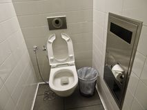 Clean well maintained toilet at the airport. White toilet, trash can. And shower for washing royalty free stock photo