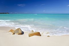 Clean White Caribbean Beach With Turquoise Water, Antigua. A clean white caribbean beach with deep blue sky and turquoise water, some stones in the foreground Stock Photography