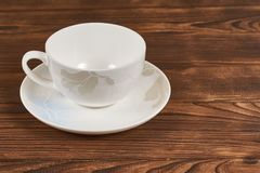 White cup and saucer. Clean white cup and saucer with delicate ornament on wooden background Royalty Free Stock Images