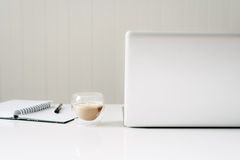 Clean white desk with laptop, diary and coffee Royalty Free Stock Images