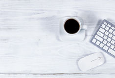 Clean white desktop with simple computer peripherals and coffee Royalty Free Stock Image