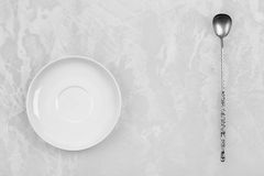 Clean white dish and an old silver spoon. On a white background Stock Photo