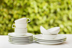 Clean dishes and cups on white tablecloth on green background Royalty Free Stock Photos