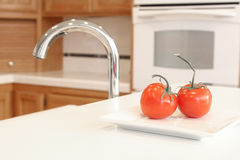 A clean white kitchen with two red tomatoes. A clean white kitchen with two red tomatoes, a kitchen sink, counters and an oven in a blurred background. Shiny Royalty Free Stock Photography