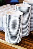 Clean white plates and cups on a wooden table Royalty Free Stock Photography