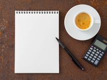 Clean white sheet in an open spiral-bound pad, pen, calculator a. Nd Cup of coffee on the iron of the rusty metal table, top view Royalty Free Stock Image