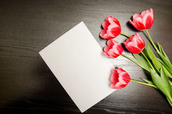 Clean white sheet of paper and pink tulips on a black wooden background. top view, space for text Stock Photography