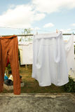 Clean white shirt and orange pants (trousers) hanging to dry. Housework, laundry in sunny day stock images