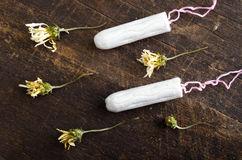 Clean white tampons lying on wooden surface with Royalty Free Stock Photos