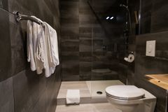 Clean white towels on a hanger at bathroom against grey wall tiles Stock Photo