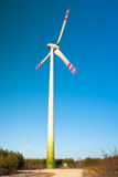 Clean Wind Energy. Wind farm turbine in motion generating clean power energy - alternative power source Royalty Free Stock Image
