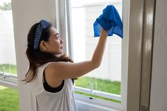 Clean window of new house by microfiber fabric. Cute Asian woman or Housewife using blue microfiber cloth to cleansing window or mirrror of new home after moving royalty free stock photography
