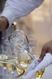 Clean wine glass. The waiter remove wine glasses after a banquet Royalty Free Stock Photography