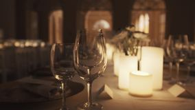 Clean wine glasses on dinner table with lit candles and plates at banquette stock footage