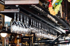 Clean wine glasses hanging ready in a bar Stock Image