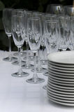 Clean wineglasses  with plates. Clean wineglasses with plates on the white table in the restaurant Royalty Free Stock Photos