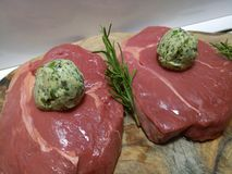 Two raw rump steaks with garlic butter and rosemary Stock Image