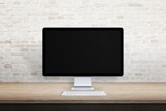 Clean workplace with computer display. Blank screen for web site promotion. Empty desk and brick wall Royalty Free Stock Images