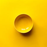 Clean yellow bowl. New clean yellow bowl on yellow background. Top view Stock Images