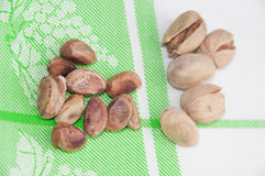 The cleaned roasted pistachios over green tablecloth Stock Photo