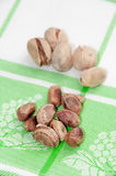 The cleaned roasted pistachios over green tablecloth Stock Photos