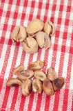 The cleaned roasted pistachios over red tablecloth Stock Photo