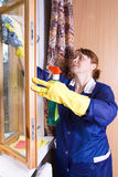 Cleaner. The woman in overalls washes a window Royalty Free Stock Images