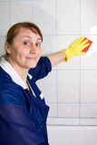 Cleaner. The woman wipes a rag a tile Royalty Free Stock Photography