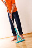 Cleaner. The teenager in an orange T-shirt washes a floor stock photos