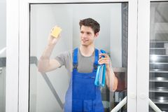 Cleaner Cleaning The Door Glass Royalty Free Stock Photography