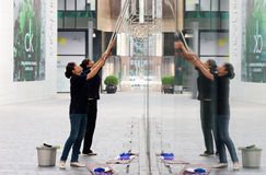 Cleaner cleaning glass of buildings Royalty Free Stock Image