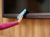 Cleaner from cleaning service is cleaning dirt and dust from tv Royalty Free Stock Images