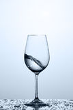 Cleaner and freshness water wave in the wineglass while standing on the glass against light background. Cleaner and freshness water wave in the wineglass while Stock Photos