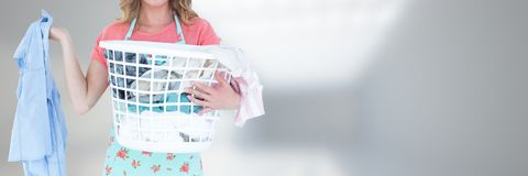 Cleaner with laundry basket and bright background Stock Photography