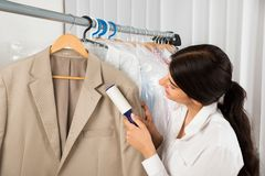 Cleaner in laundry shop with adhesive roller Royalty Free Stock Image