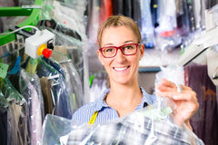 Cleaner in laundry shop checking clean clothes Stock Photo