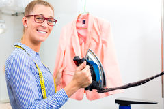 Cleaner in laundry shop ironing jacket Stock Images